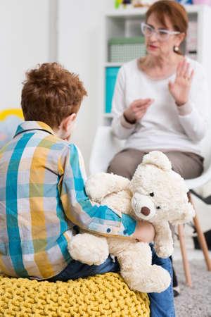 Petit garçon tenant un ours en peluche, assis sur un pouf jaune et être présenté le langage des signes par une femme d'âge moyen en arrière-plan flou