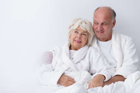 infatuation: Elderly couple is sitting snuggled relaxed in bed in the morning