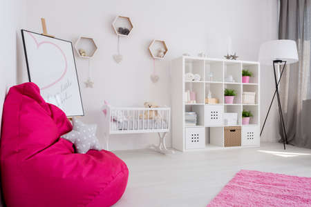 baby sit: Bright and spacious baby girls room with white furniture and a large fuchsia sit sack in the first ground Stock Photo