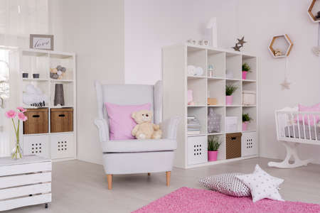 idea comfortable: White wing chair in a cute baby room, surrounded with baby room furniture and pastel decorations Stock Photo