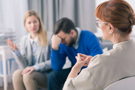 devastated: Wife explains something to the therapist and the husband is devastated during marital therapy Stock Photo