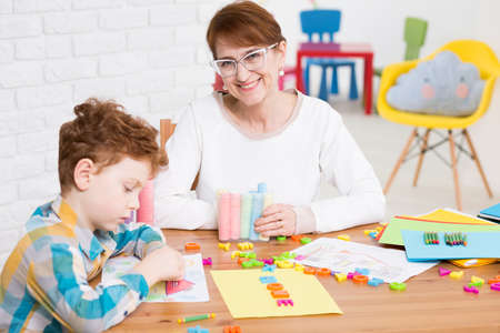 art therapy: Smiling middle-aged woman sitting at a wooden table full of plastic letters and drawing accessories, where a little red-haired boy is drawing Stock Photo