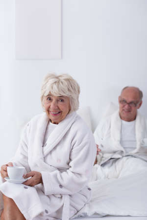 fondness: Smiling elderly woman in a bathrobe is sitting on the bed when her husband is still lying in bed Stock Photo
