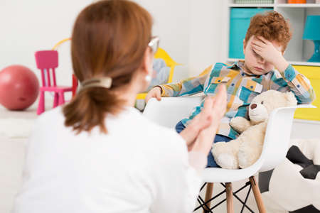 psychologists: Little boy in a child psychologists office, holding his head with his hand as if he was very bored