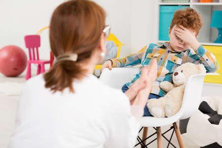 자식 심리학자의 사무실에서 그의 손으로 그의 머리를 들고하는 어린 소년 그는 매우 지 루했다