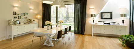 a detached living room: Very spacious and elegant dining room in a luxurious house with a large terrace window overlooking the forest