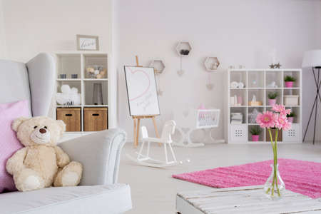accessories horse: Close-up of a cozy armchair with a teddy bear in a cute little girls room Stock Photo