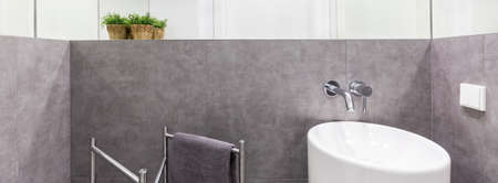 bidet: Ceramic bidet unit installed in a luxurious bathroom with grey tiles and a folding towel rail beside