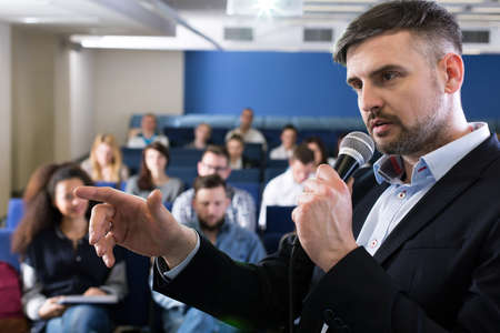 smartly: Close-up of a young academic teacher holding a microphone and pointing at something during college classes