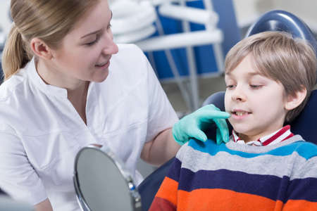 stomatologist: Young stomatologist showing to the patient mirror to allow him to see the dentition