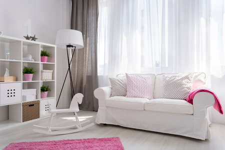 accessories horse: Corner of a bright baby room in white and pink with a large window and a cosy sofa beside Stock Photo