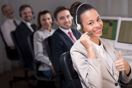 professionalist: Young female consultant is smiling and performing a thumb up gesture. At the background her co-workers are also smiling Stock Photo