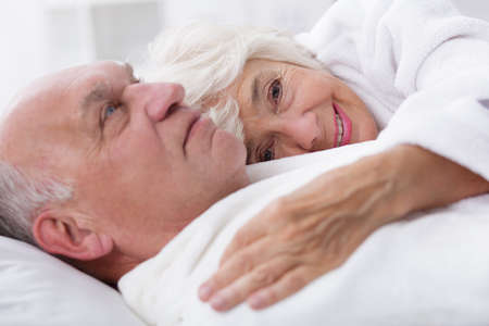 fondness: Older spouses are snuggled in bed in the morning Stock Photo