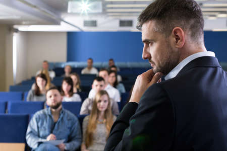 lecture theatre: Profile shot of a young, smartly-dressed academic teacher in a lecture room, with a very concentrated look on his face Stock Photo