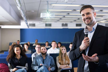lecture theatre: Smiling college teacher with a microphone, standing against a background of a group of students in a lecture hall Stock Photo