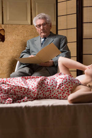 psychoanalysis: Senior psychotherapist looks at the note while his female patient is lying on a couch during the session