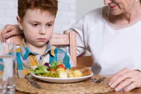 Nahaufnahme eines kleinen Jungen böswillig bei einem großen Teller voll von gesunden Nahrungsmitteln suchen