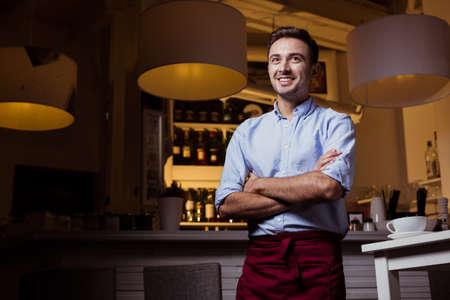 Joven, sonrió camarero en el interior del restaurante, de pie cerca de la barra con estanterías llenas de vino detrás