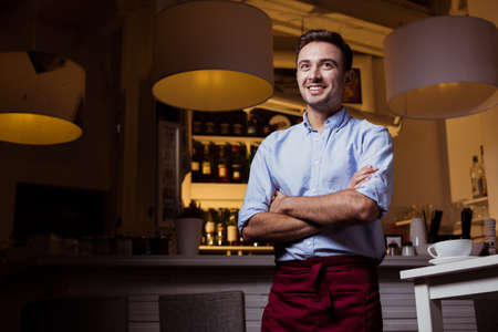 Young, smiled waiter in restaurant interior, standing close to the bar with shelves full of wine behind