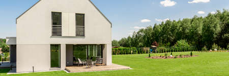 Sunny panoramic view of a modern detached house outside the city, with a large lawn and the forest behind the fence Stock Photo