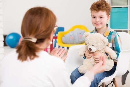 Záběr úsměvem malého chlapce sedí v bílém křesle a držel si medvídka, když mluví do dětského psychologa