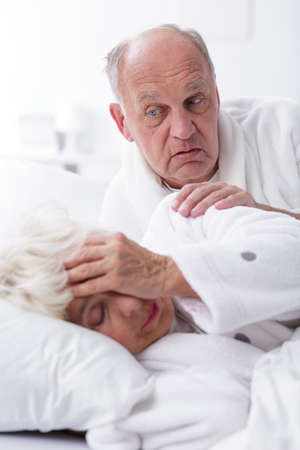 infatuation: Worried older man touches the arm of his wife who is holding her head  Stock Photo