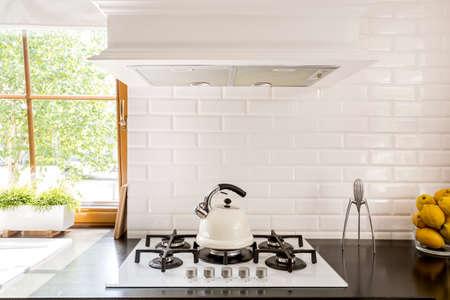 Nieuwe stijl keuken met donker werkblad, witte gasfornuis en decoratieve baksteen backsplash