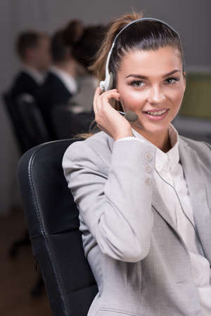 professionalist: Young female telephone consultant sitting on a chair and listening to a client voice in headphones Stock Photo