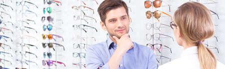 man doctor: Shot of a young man standing against a wall full of glasses