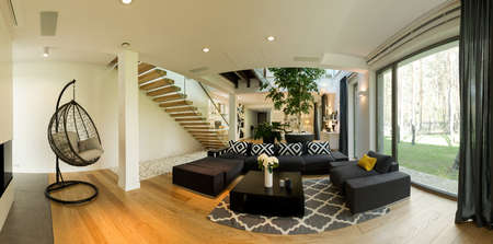corner house: Very roomy ground floor of a contemporary designer house, with a large black lounge and a hanging chair