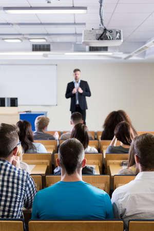 Interior de una sala de conferencias brillante con un grupo de estudiantes, visto desde la parte de atrás, escuchando a un profesor académico