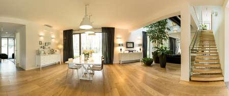 Holle binnenland van een moderne vrijstaande woning met een eetkamer samen met de woonkamer en luchtige trap Stockfoto
