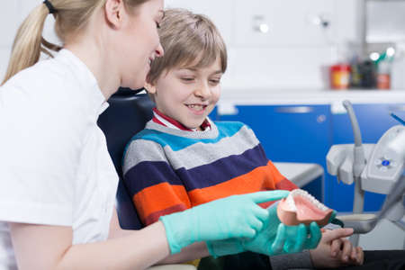 stomatologist: Young stomatologist sitting close to the little boy patient at dentists office showing him a jowl model