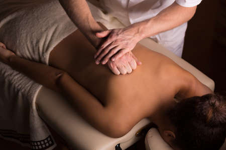 massage table: Young woman having healthy back massage, lying on a professional massage table