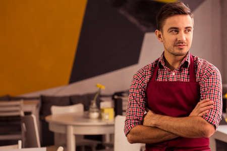 mandil: camarero joven en interior del restaurante con los brazos cruzados y restaurantes mesas y sillas en el fondo