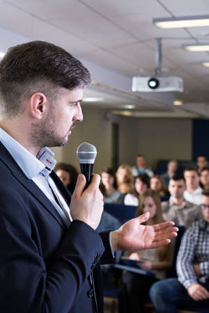 lecture theatre: Close-up of a young teacher delivering a lecture in a lecture room filled with students