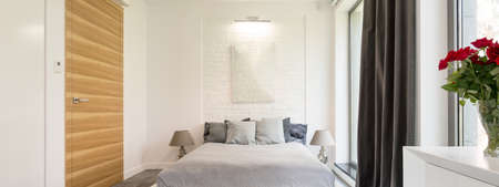 bedroom wall: Very bright designer bedroom in white and grey with partially brick wall and a large window Stock Photo