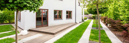 Panoramic picture of a white detached house sourounded by trees Stock Photo