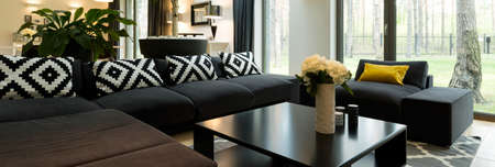 a detached living room: Luxurious lounge room overlooking the forest, with a large black corner sofa and a black coffee table