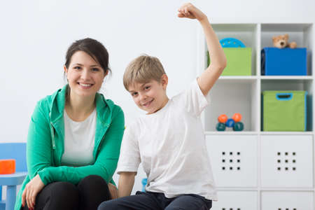 boy lady: Young smiled physiotherapist sitting close to the young boy taking lifted arm