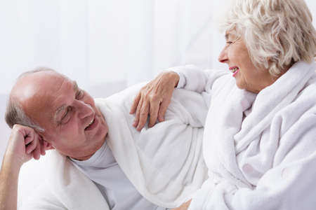 infatuation: Older smiling woman touches the arm of her husband who is lying in bed