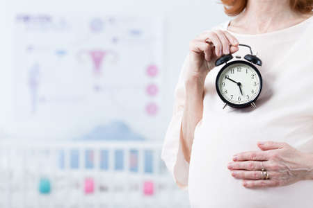 Close-up of woman after forties in pregnant holding the ticking clock