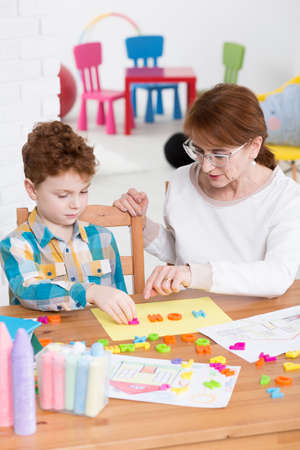 Red-haired schoolboy sitting at a wooden table, learning alphabet with plastic letters, assisted by a middle-aged woman