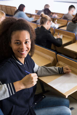 lecture theatre: Smiling young student in a lecture theatre with an exam answer sheet in front of her Stock Photo