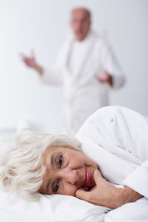 senility: Sad old woman is lying in bed when her husband is standing and gesturing Stock Photo