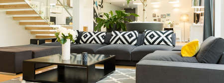 a detached living room: Very large and stylish black corner sofa with a designer coffee table, next to stairs with glass railing