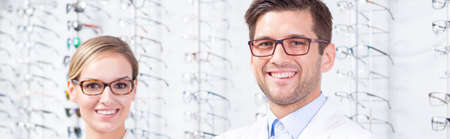 Panoramic picture of two optometrists standing against a wall with glasses display