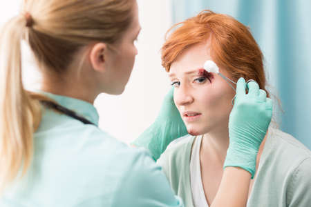 gloves nurse: Shot of a sad girl having her wounds cleaned in an emergency room Stock Photo