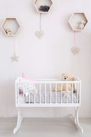 white heart: Close-up of a white cradle in a very bright baby room, with subtle decorations on the wall