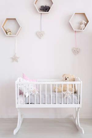 Nahaufnahme einer weißen Wiege in einem sehr hellen Babyraum, mit subtilen Dekorationen auf der Wand Standard-Bild